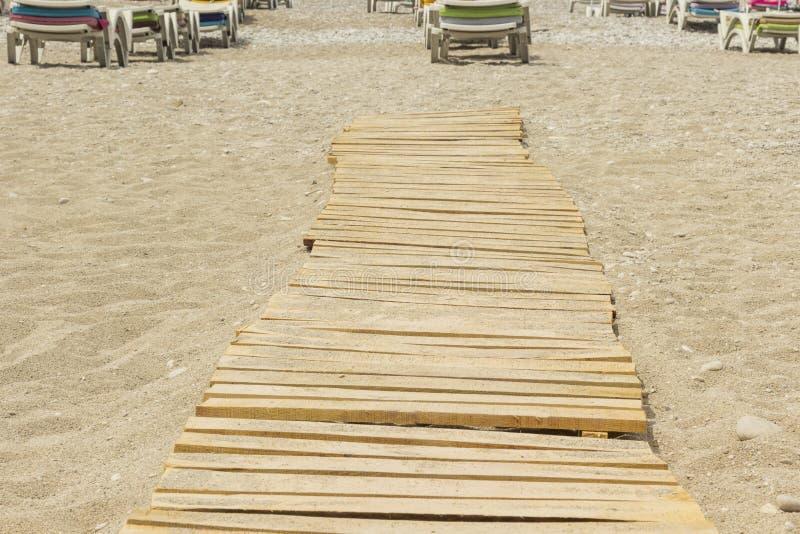 Zandig strand, houten raad, zitkamerstoelen in de afstand royalty-vrije stock foto's