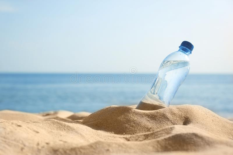 Zandig strand met fles het verfrissen van drank op hete de zomerdag stock afbeelding