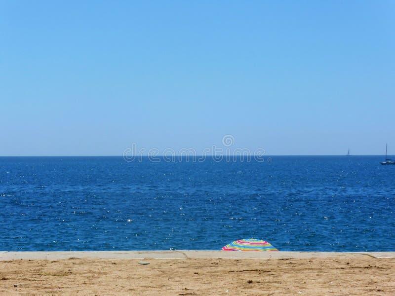 Zandig strand met kristal blauwe overzees met eenzame paraplu in afstand stock foto's