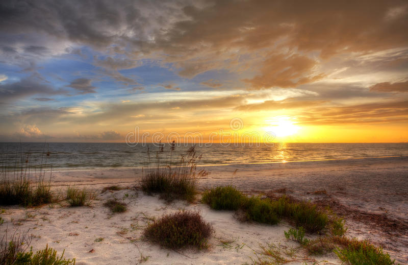 Zandig strand met zonsondergang stock foto