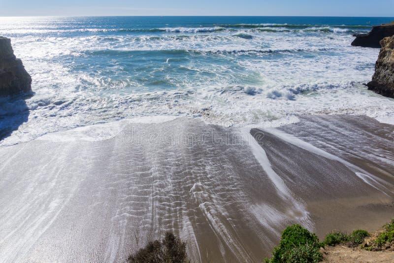 Zandig strand op de Vreedzame Oceaankust tijdens vloed en sterke branding, Wilder Ranch State Park, Californië stock fotografie