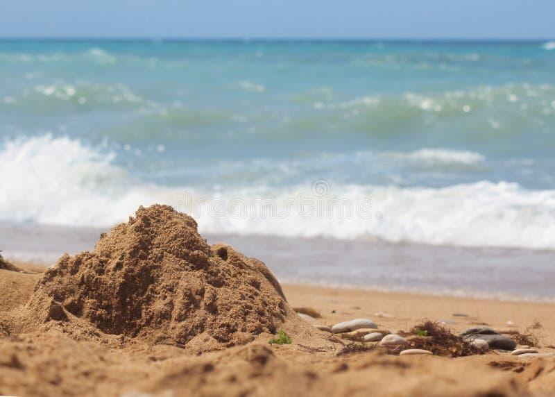 Zandig strand tegen de blauwe hemel en overzeese golven, vóór het het naderbij komen onweer Water en zanddetail royalty-vrije stock foto