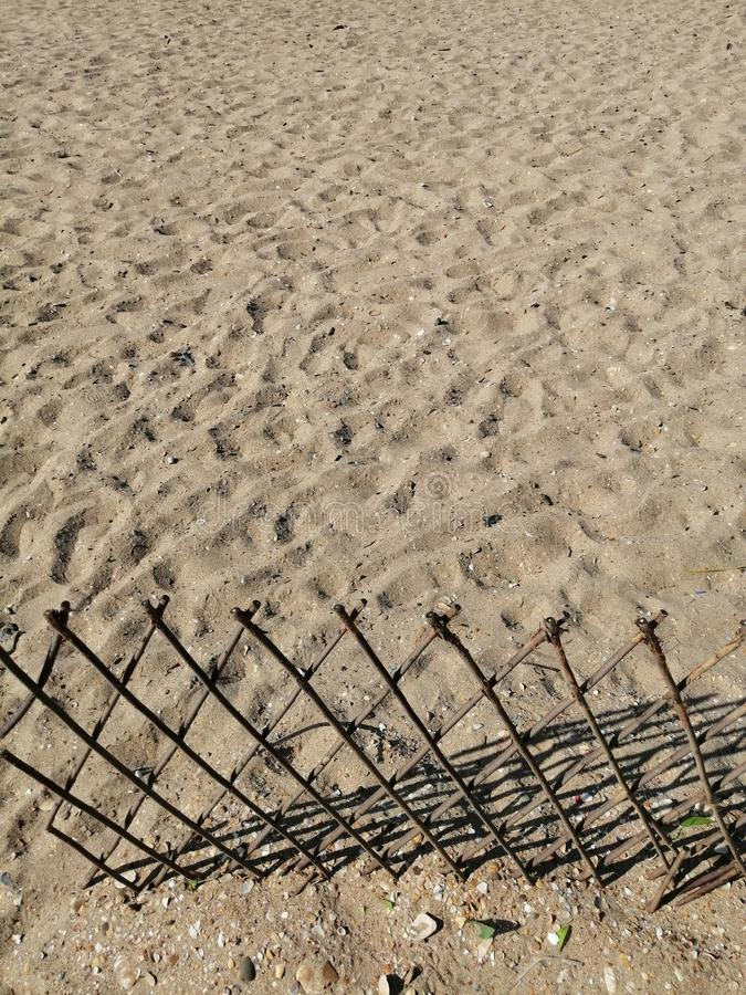 Zandig strand, zandachtergrond en houten omheining stock afbeeldingen