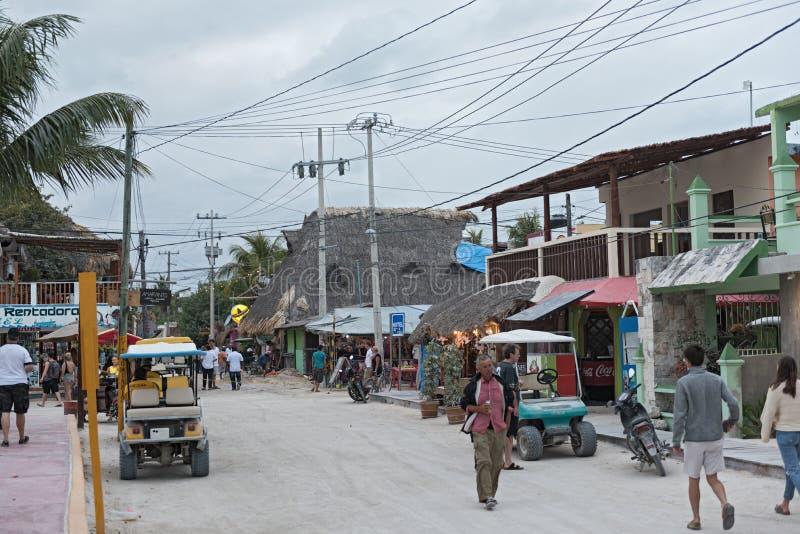 Zandige die weg met toeristen en boxen op Holbox-Eiland, Quintana Roo, Mexico in schiereiland het Noord- van Yucatan wordt gevest royalty-vrije stock afbeelding