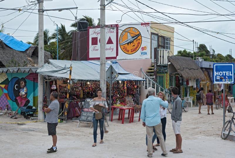 Zandige die weg met toeristen en boxen op Holbox-Eiland, Quintana Roo, Mexico in schiereiland het Noord- van Yucatan wordt gevest stock fotografie