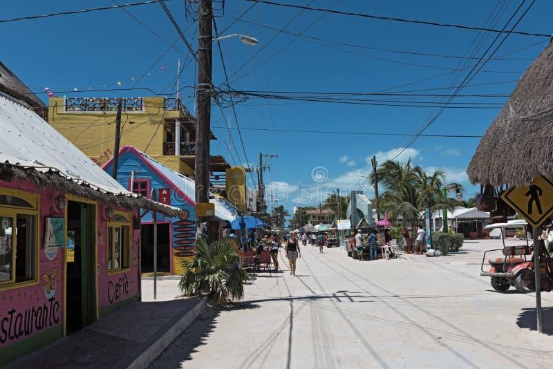 Zandige die weg met toeristen en boxen op Holbox-Eiland, Quintana Roo, Mexico in schiereiland het Noord- van Yucatan wordt gevest stock afbeeldingen