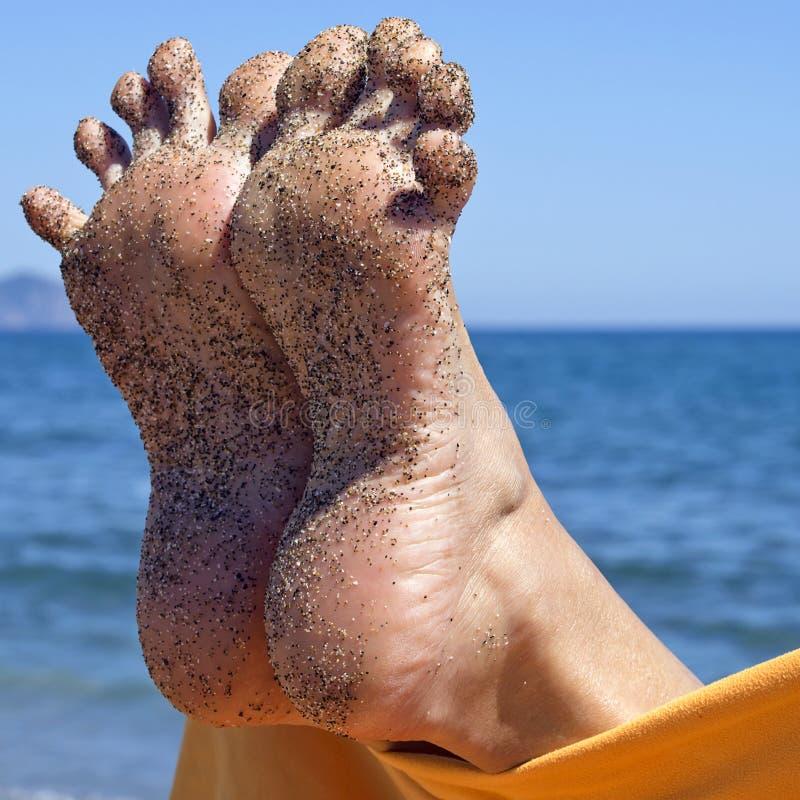 Zandige gekke vrouwentenen op het strand stock foto's