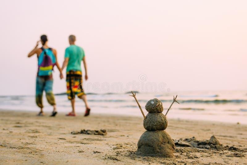 Zandige gelukkige mens op het overzeese strand tegen homoseksuelenpaar het lopen royalty-vrije stock afbeeldingen