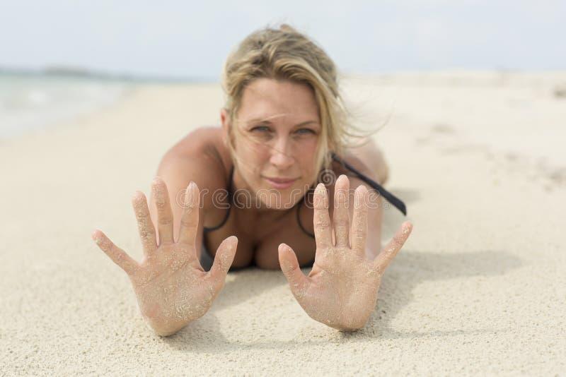 Zandige handen Een mooie blondevrouw legt bij het strand stock foto's