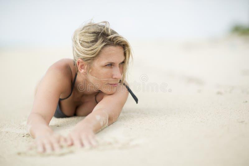 Zandige handen Een mooie blondevrouw legt bij het strand stock foto