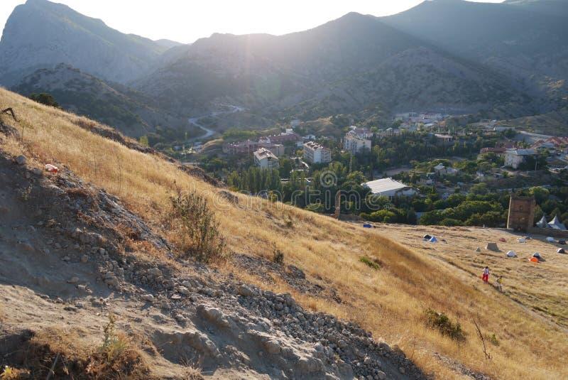 Zandige hellingen op de achtergrond van een comfortabele die stad en hooggebergte met gras wordt behandeld royalty-vrije stock foto