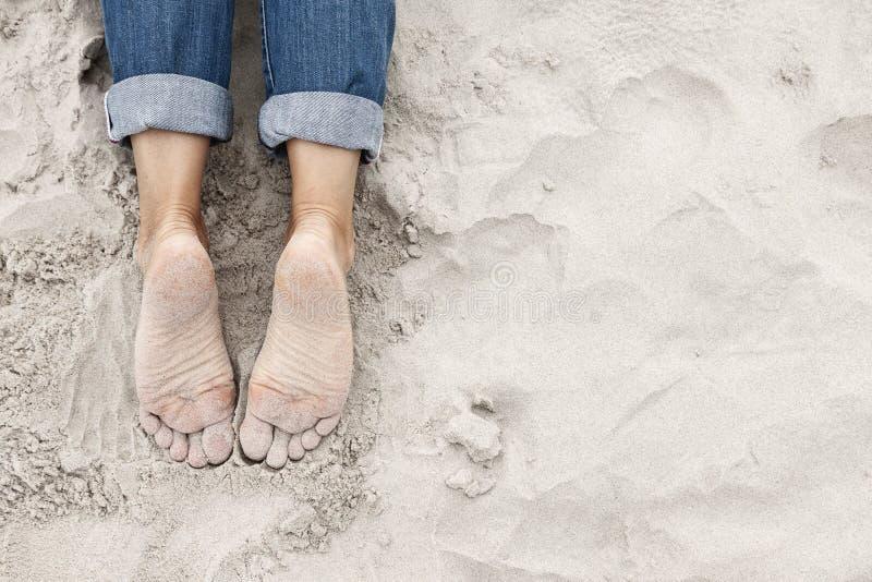Zandige jonge vrouwenvoeten op het strand stock afbeelding