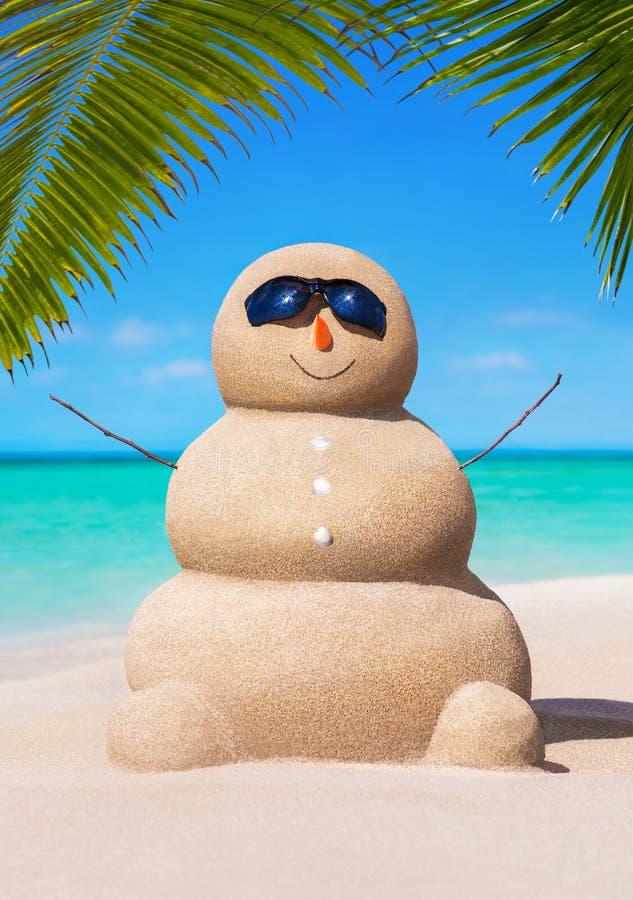 Zandige sneeuwman in zonnebril in tropisch zonnig oceaanpalm beach stock fotografie