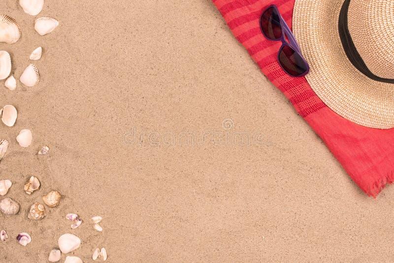 Zandige strandachtergrond, zonnebril, hoedenzeeschelpen stock foto's