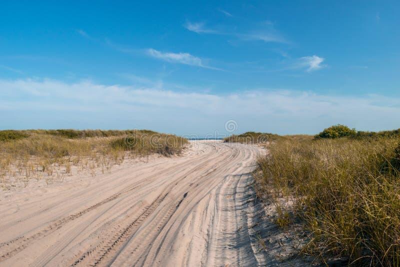 Zandige weg die naar de Atlantische Oceaan, onder een mooie duidelijke blauwe hemel, Brandeiland, NY leiden stock afbeeldingen