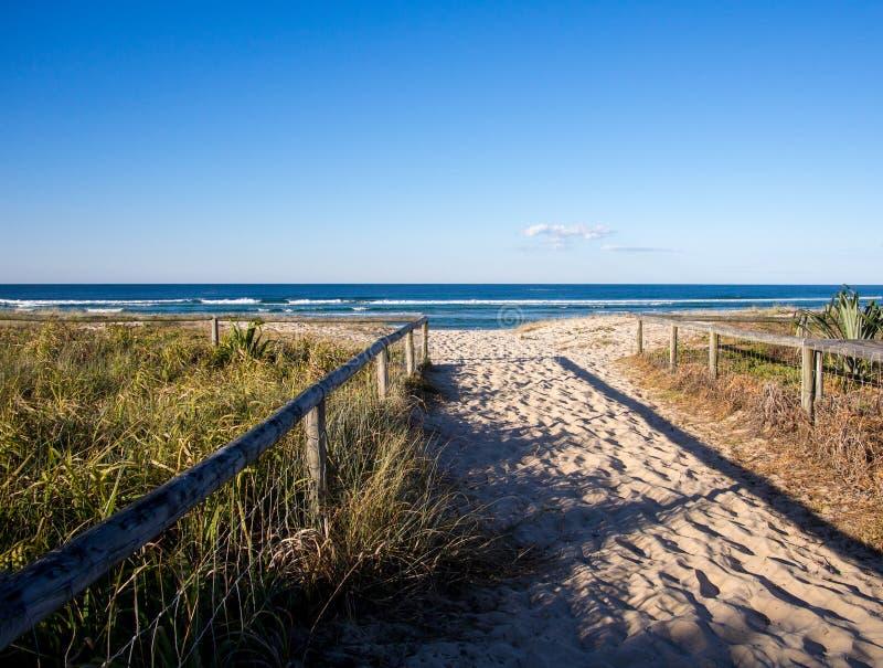 Zandige wegingang aan het strand met houten sporen Gouden Kust Australië stock foto