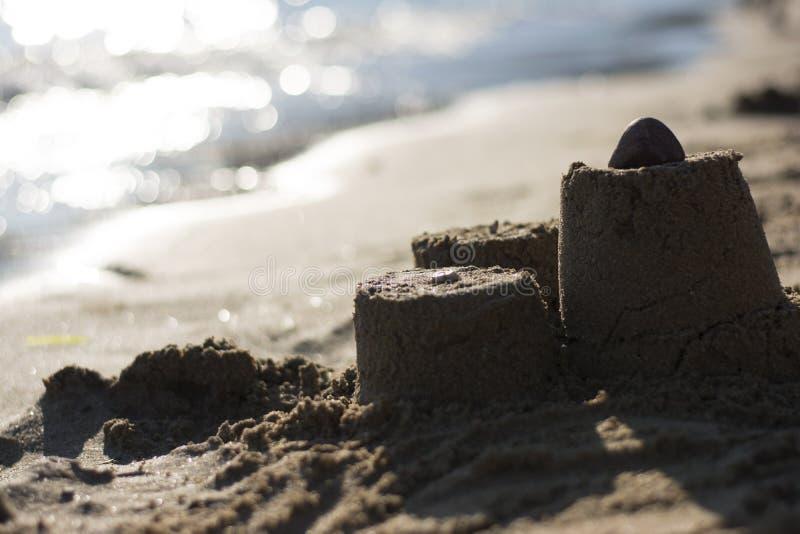 Zandkasteel op het strand bij zonsondergang stock foto's