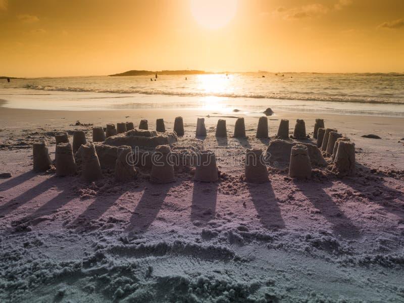 Zandkasteel op het strand in de stralen van de zonsondergang stock fotografie