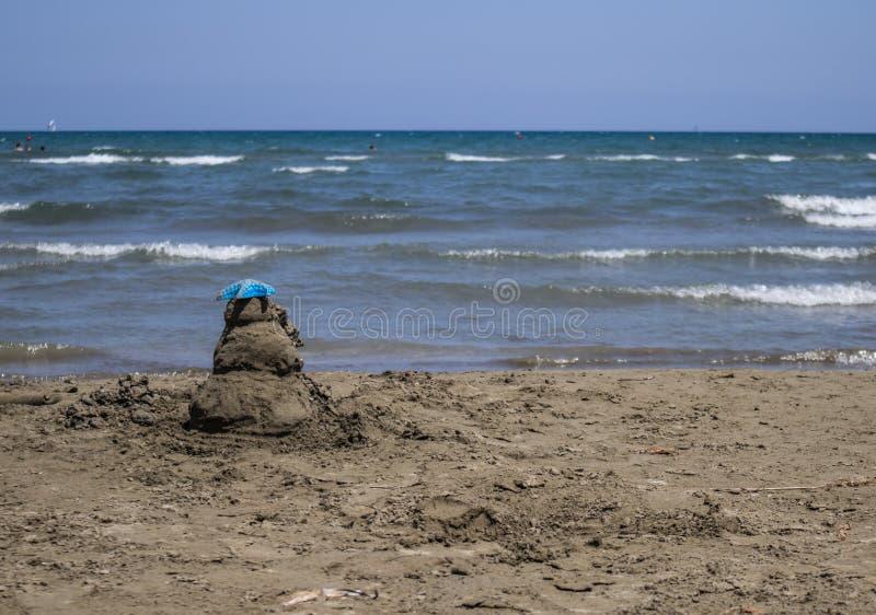Zandkasteel op het strand met blauwe hemel en overzees stock foto's