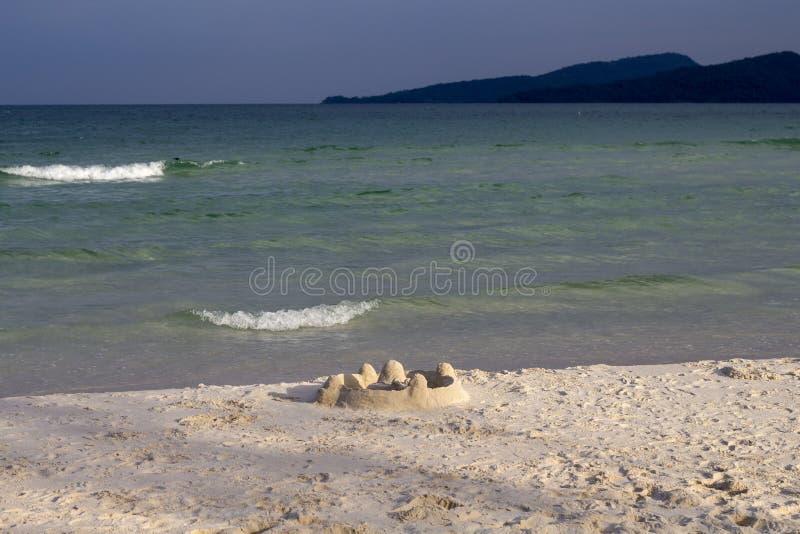 Zandkasteel op strand in zonsonderganglicht Tropisch kustlandschap met wit zandstrand royalty-vrije stock foto