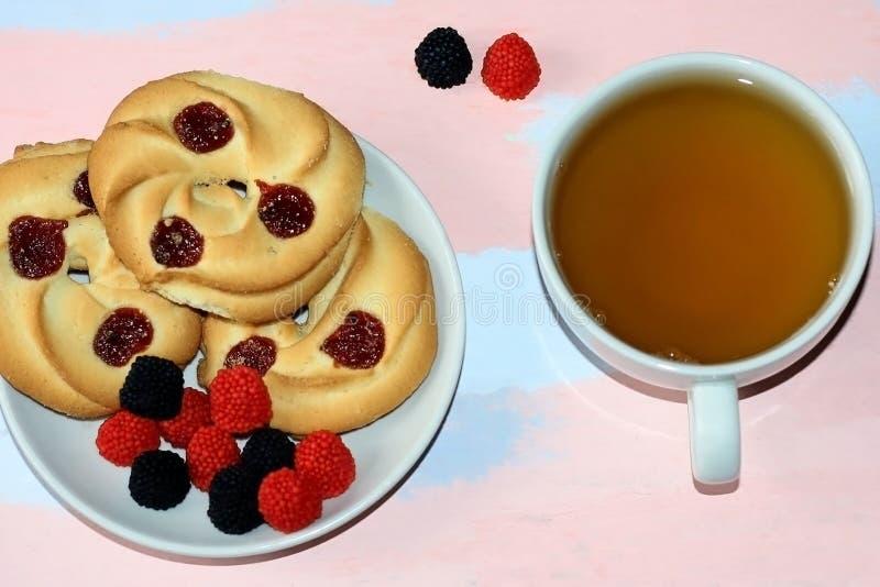 Zandkoek met rode en zwarte bessen en een kop van groene thee op een lichte achtergrond stock afbeeldingen