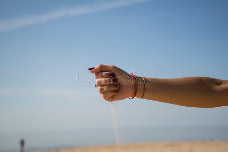 Zandlooppas vanaf de handen stock fotografie