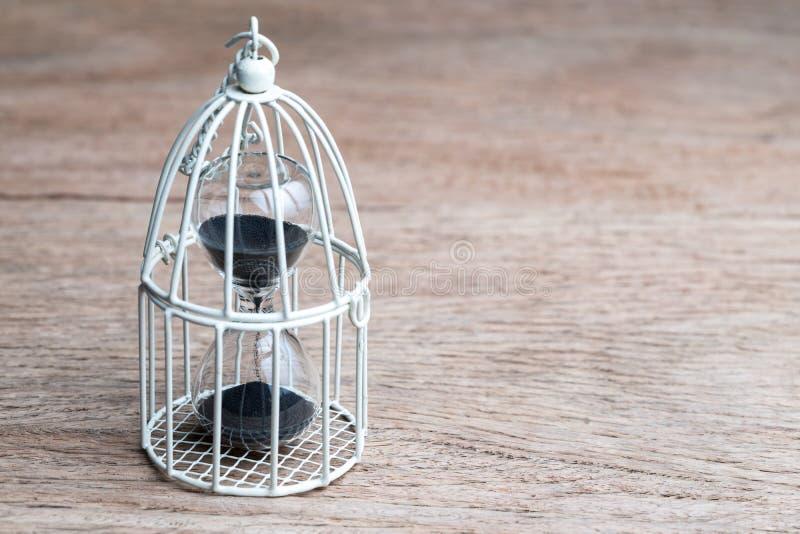Zandloper en sandglass in miniatuurvogelkooi met exemplaar het ruimte gebruiken als tijdcontrole of beperkt van tijdconcept royalty-vrije stock afbeeldingen