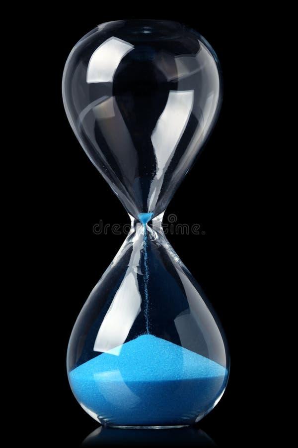 Zandloper met blauw zand die de passage van tijd tonen royalty-vrije stock afbeelding
