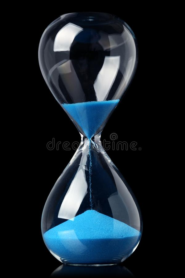 Zandloper met blauw zand die de passage van tijd tonen royalty-vrije stock foto