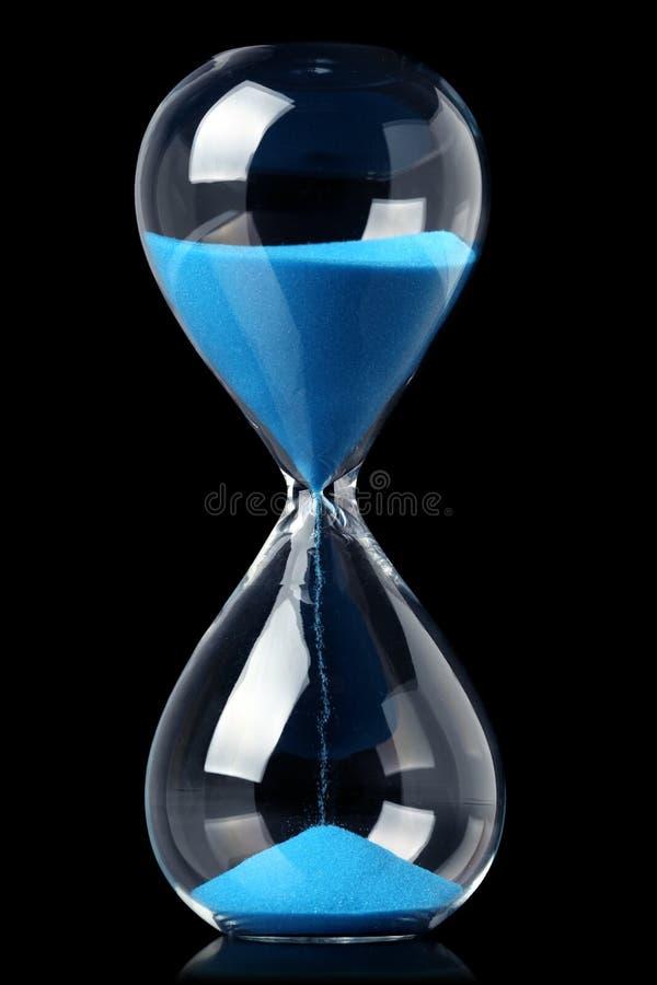Zandloper met blauw zand die de passage van tijd tonen stock foto