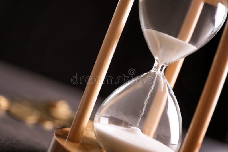 Zandloper met stromend zand op lijst Vector moderne illustratie in vlakke stijl met de mannelijke chronometer van de handholding stock foto