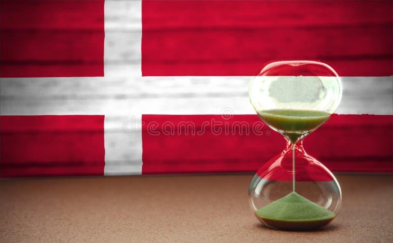 Zandloper op de achtergrond van de vlag van Denemarken, het concept tijd en landen, ruimte voor tekst royalty-vrije stock foto's