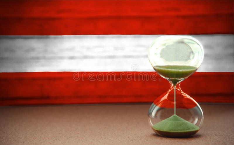 Zandloper op de achtergrond van de vlag van Oostenrijk, het concept tijd en landen, ruimte voor tekst stock fotografie