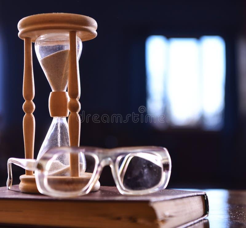 Zandloper, oude boek en oogglazen op houten lijst, donkere achtergrond Zand die onderaan binnen van zandloper vallen Tijdstroom royalty-vrije stock foto
