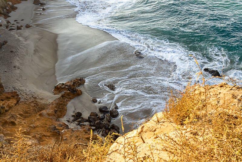 Zandsteenweg die klippen zij, pacfic oceaangolven op een zandig strand overzien, rotsen royalty-vrije stock fotografie