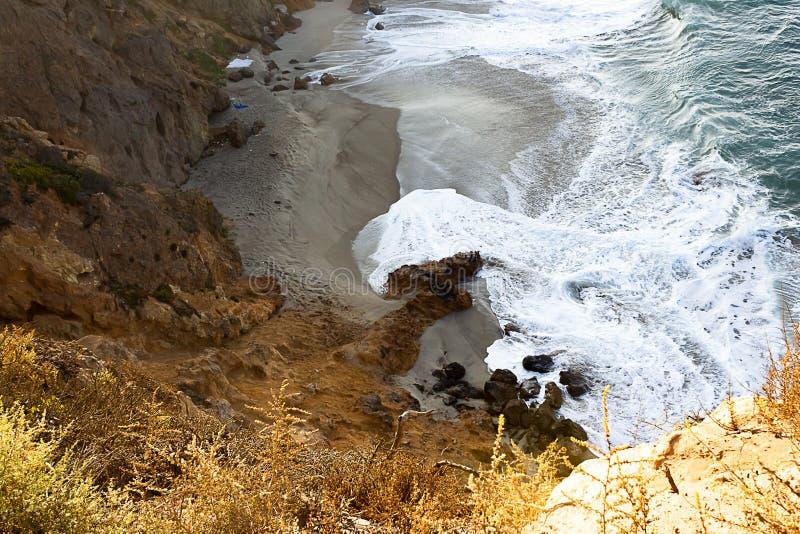 Zandsteenweg die klippen zij, pacfic oceaangolven op een zandig strand overzien, rotsen royalty-vrije stock foto's