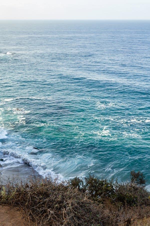 Zandsteenweg die klippen zij, pacfic oceaanuitgestrektheid, en golven op de kust overzien stock foto