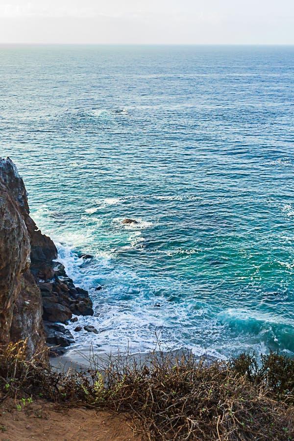 Zandsteenweg die klippen zij, pacfic oceaanuitgestrektheid, en golven op de kust overzien stock foto's