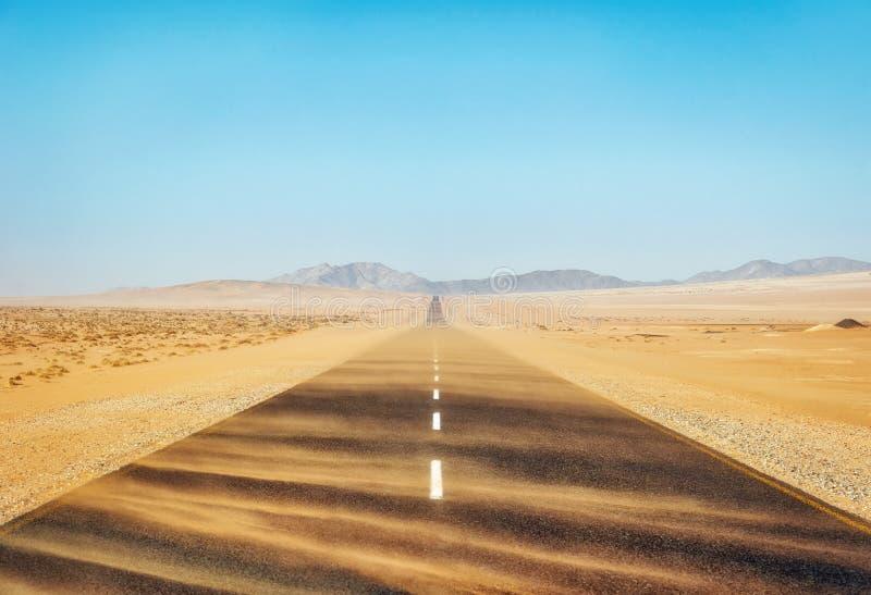 Zandstorm over Eenzame Woestijnweg in Zuidelijke Namibië genomen I stock foto