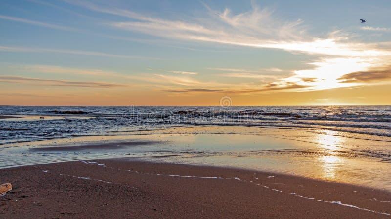 Zandstrand met eindeloze horizon en schuimende golven onder de heldere zonsondergang met gele kleuren en wolken boven het overzee stock afbeeldingen