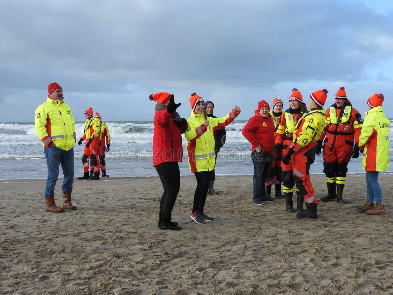 Zandvoort, die Niederlande - 1 Januari 2019: traditionelle neue Jahre Dive Nieuwjaarsduik Tanzende Wasserrettungsmannschaft Reddi lizenzfreie stockfotografie