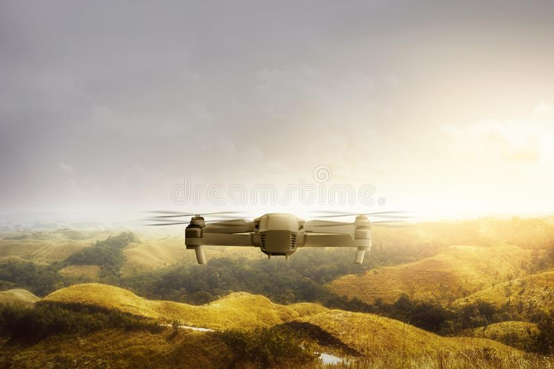 Zangão branco com voo da câmera acima dos montes verdes e das árvores fotografia de stock