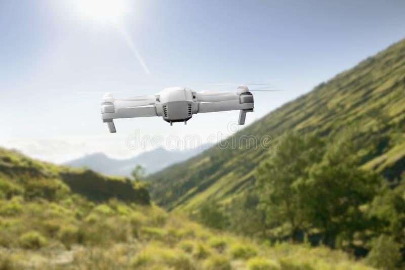 Zangão branco com voo da câmera acima da montanha com grama verde e das árvores com luz solar foto de stock