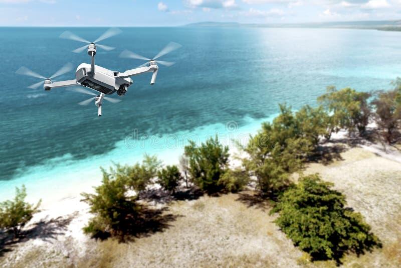 Zangão branco com voo da câmera sobre a praia com árvores verdes e o oceano azul fotografia de stock