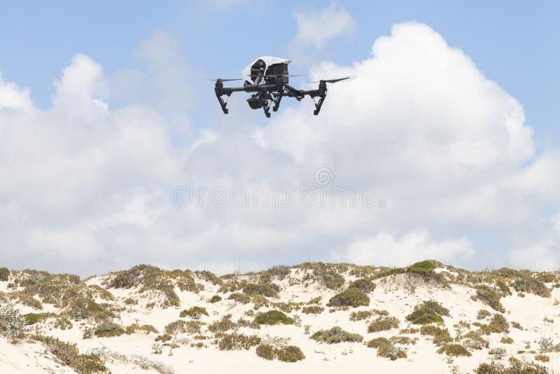 Zangão branco do quadcopter com a câmera da foto sobre as dunas foto de stock