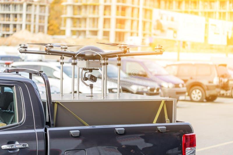 Zangão feito-à-medida grande sobre o tronco do caminhão do picup Canteiro de obras pesado do hexacopternwith do UAV no fundo Comm fotografia de stock