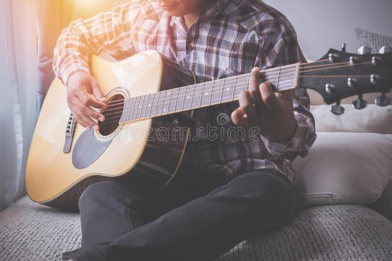 Zanger het spelen gitaar op bed stock fotografie