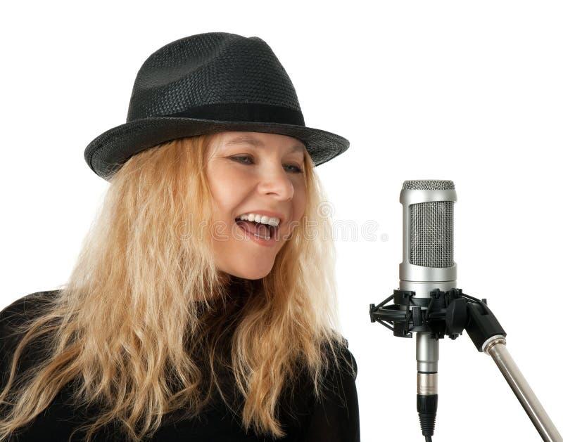 Zanger in het zwarte hoed zingen met de microfoon stock fotografie