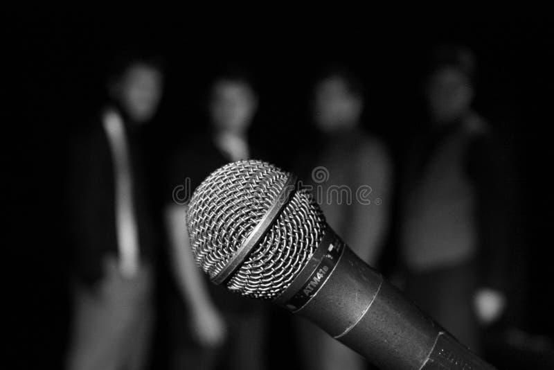 Zangers achter mic stock afbeeldingen