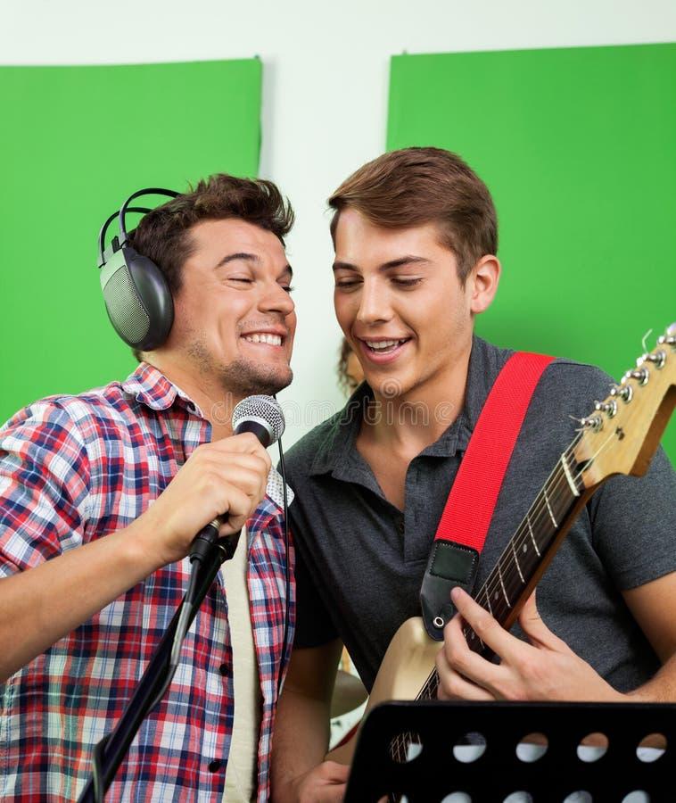 Zangers die met Microfoon en Gitaar in Opname Studi presteren stock foto